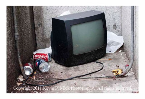 Television and trash in building alcove