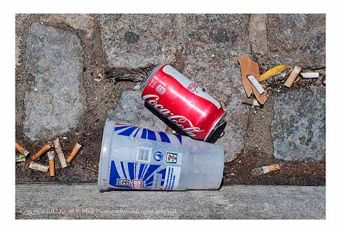Soda can and plastic cup in gutter