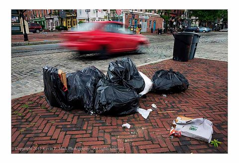 Trash bags piled near street