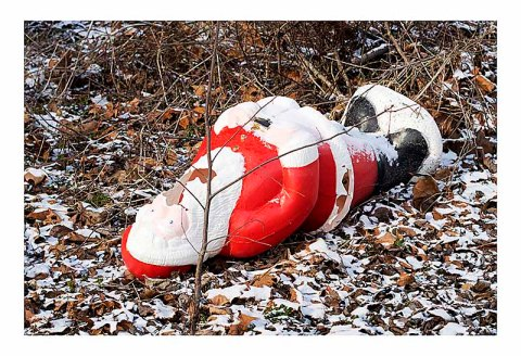 Broken plastic Santa in the woods.