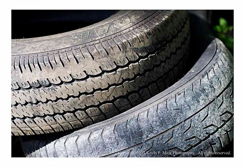 Closeup of two tires thrown in woods.