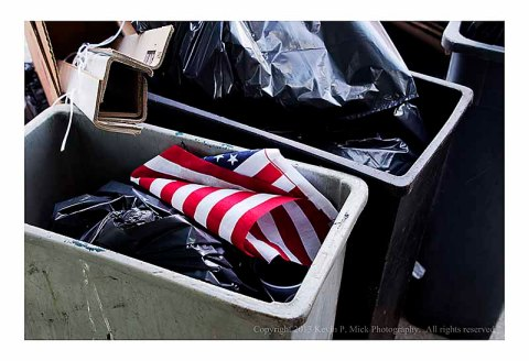 American flag thrown in trash can.