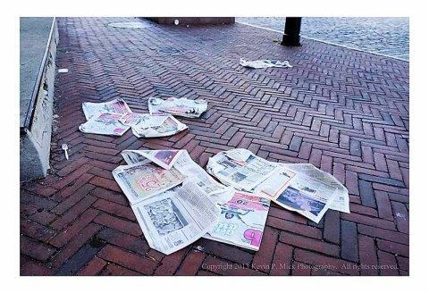 Newspapers strewn along sidewalk.