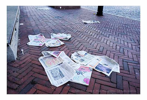 Newspapers strewn along sidewalk.