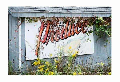 Faded produce sign on old building.