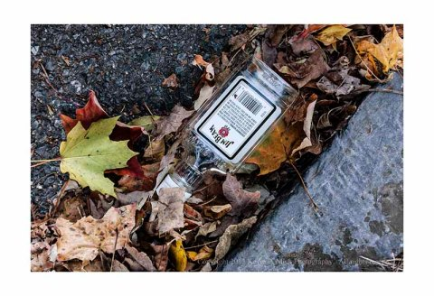 Empty Jim Beam bottle in the gutter.
