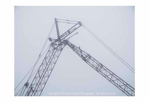 Two cranes with crossed booms in fog.