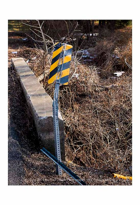 Road sign bent over concrete abutment.