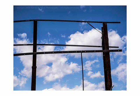 The upright frame of a fallen billboard against the sky.