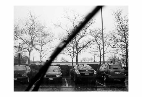 Rainy day as seen through a windshield with wiper blades at work.