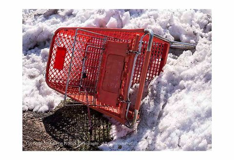 Shopping cart on its side stuck in a snowbank.
