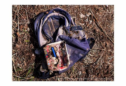Abandoned child's backpack and lego set in dirt.