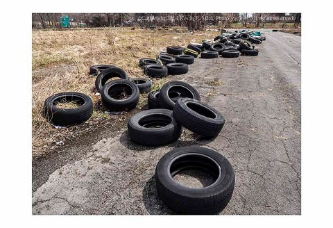 A line of abandoned tires laying in the road.