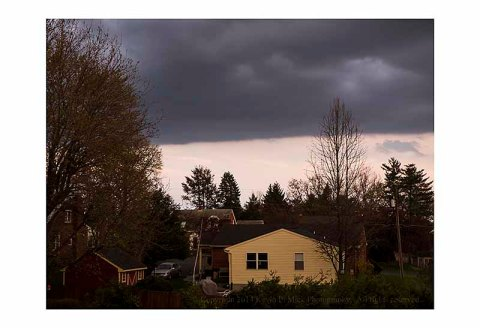 Line of heavy storm clouds over a neighborhood house.