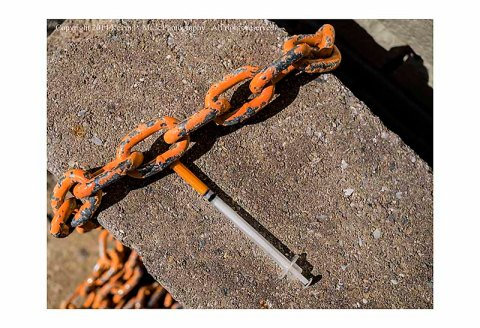 Chain overlapping a syringe on concrete block.