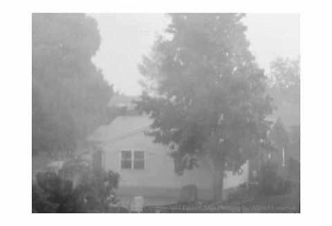 BW photograph of house and trees during thunderstorm.