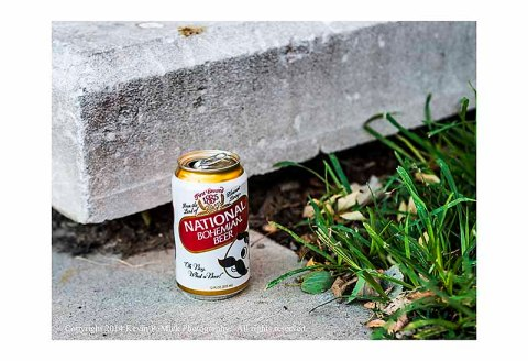 National Bohemian beer can sitting on sidewalk.