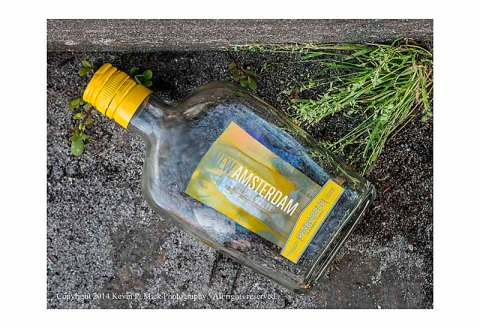 Empty New Amsterdam liquor bottle laying in gutter.