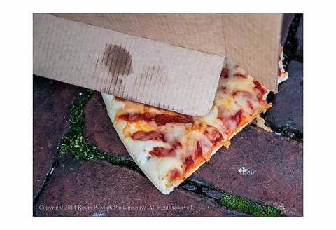 Partially eaten slice of pizza and box laying on sidewalk.