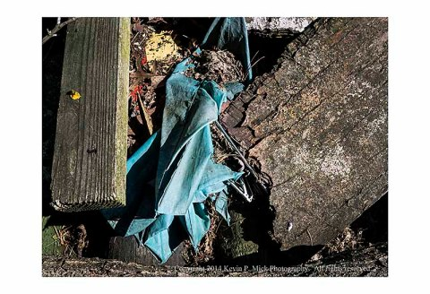 One broken abandoned blue umbrella amid building materials.