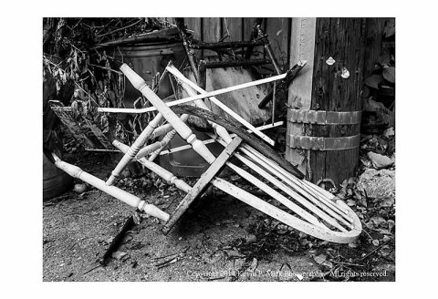 BW photograph of a broken white chair amid trash in city alley.