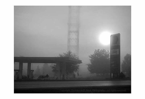 Sun rising over gas station on a foggy morning.