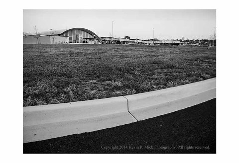 BW photograph of a parking lot grassy area.