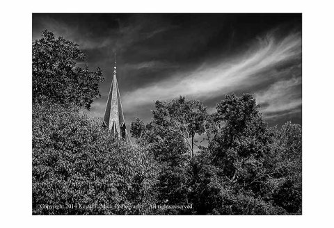 BW photograph of a church steeple, trees, and clouds.