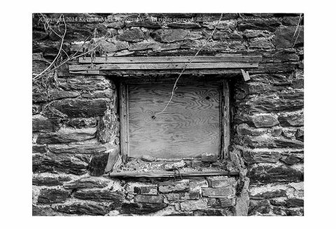 BW photography of a boarded window in a forgotten building.