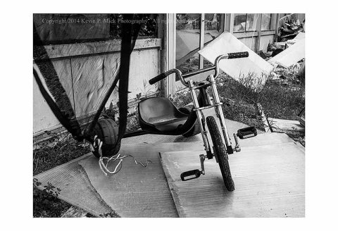BW photograph of an abandoned tricycle.