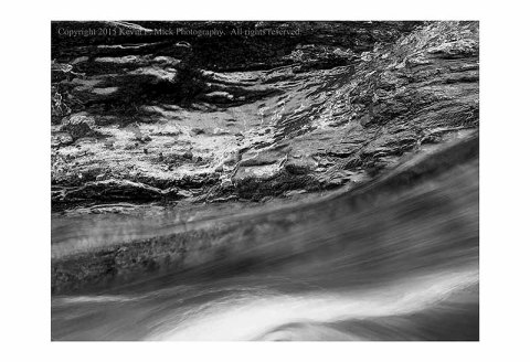 BW photograph of an ice-covered rock with fast water moving past.