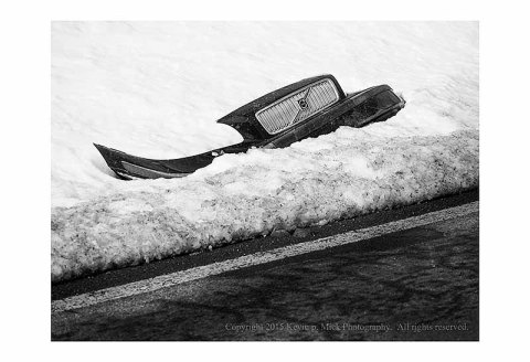 BW photograph of a crashed auto bumper in a snowbank beside a road