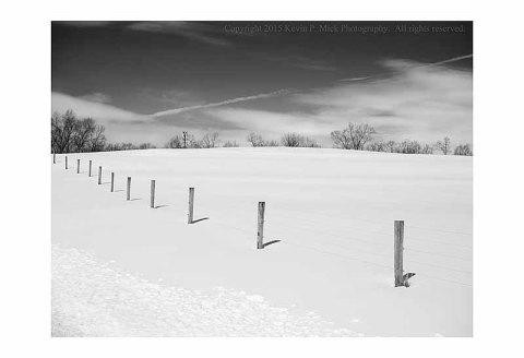 BW photograph of fence posts crossing a snow covered hill