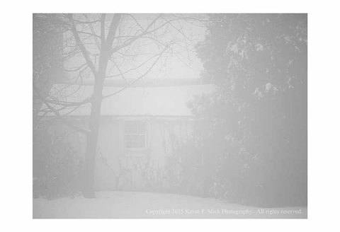 BW photograph of an old shed with snow and fog