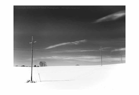 BW photograph of telephone poles across a snow covered hill