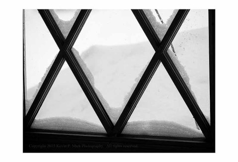 BW photograph of snow piled outside of a window.