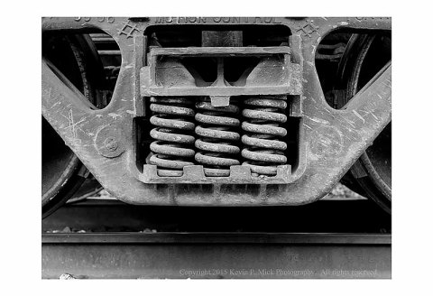 BW photograph of an idle train's truck springs