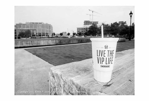 "BW photograph of a cup advertising ""Live the VIP Life"""