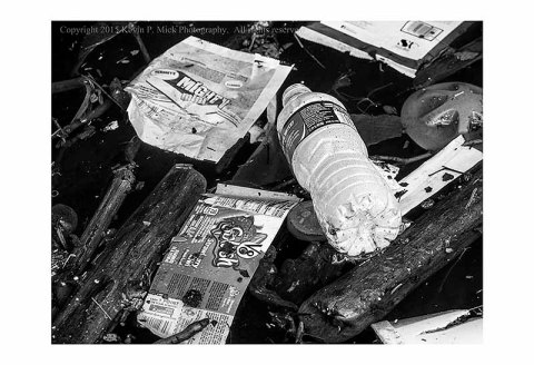 BW photograph of wood, plastic and paper trash floating in the water after July 4th