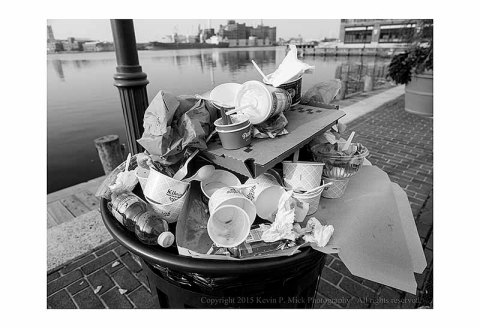 BW photograph of a trashcan overflowing with trash after July 4th