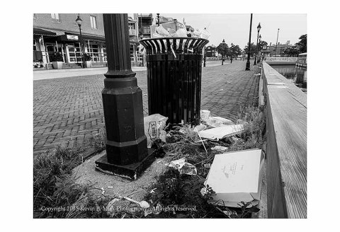 BW photograph of a trashcan overflowing onto the ground after July 4th