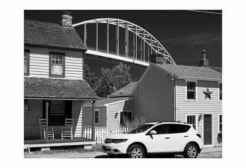 BW photograph of two houses and one car with the Chesapeake City Bridge in the background