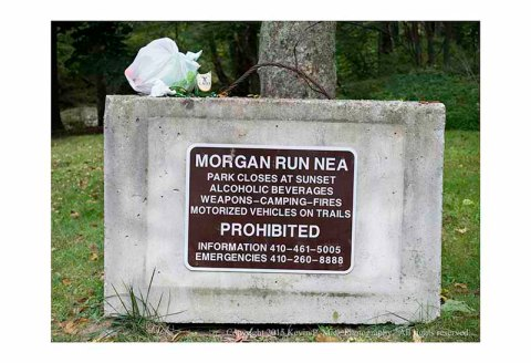 Broken beer bottle and trash bag atop concrete podium sign prohibiting alcohol at Morgan Run