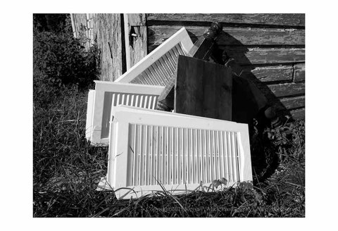 BW photograph of house shutters and a headboard leaning against an old garage