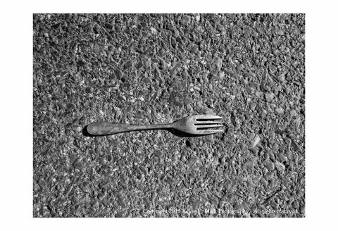BW photograph of a solitary metal fork lying in the road