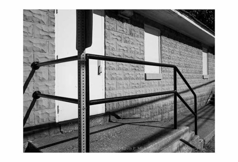 BW photograph of a black metal rail and some stairs on the side of a building