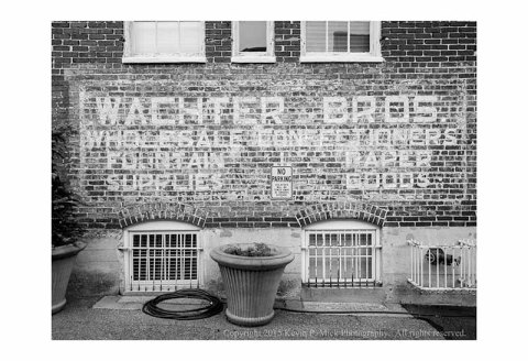 "BW photograph of a faded wall advertisement for ""Wachter Bros."""