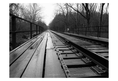 BW photograph of a rain-wetted railroad track and bridge reaching into the distance