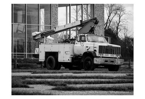 BW photograph of a boom truck in front of a building