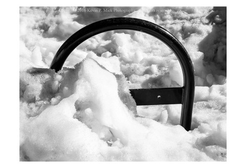 BW photograph of an iron bicycle rack half-buried in a snow bank
